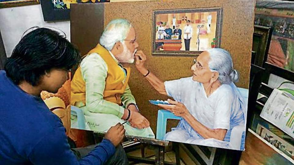 Mahesh Pandit gives finishing touches to a painting of Prime Minister Narendra Modi and his mother.