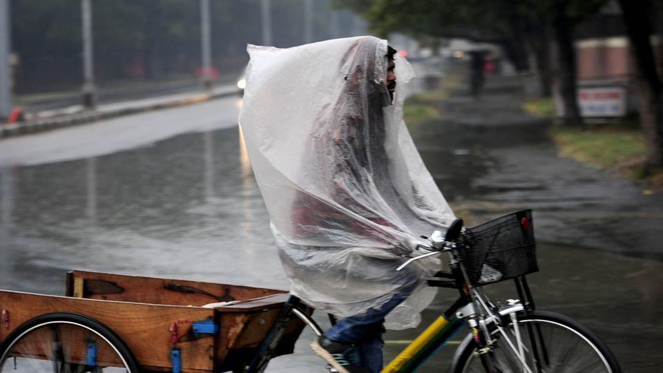 In Chandigarh, a cart puller rides his cart covering himself with plastic to keep from getting wet in rain. The meteorological department has predicted more rainfall in the region. (Keshav Singh / HT Photo)