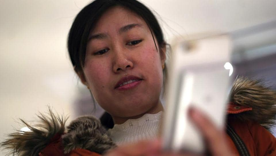 Jia Weiwei demonstrates how to play the Japanese mobile game Travel Frog on her smartphone in Beijing.