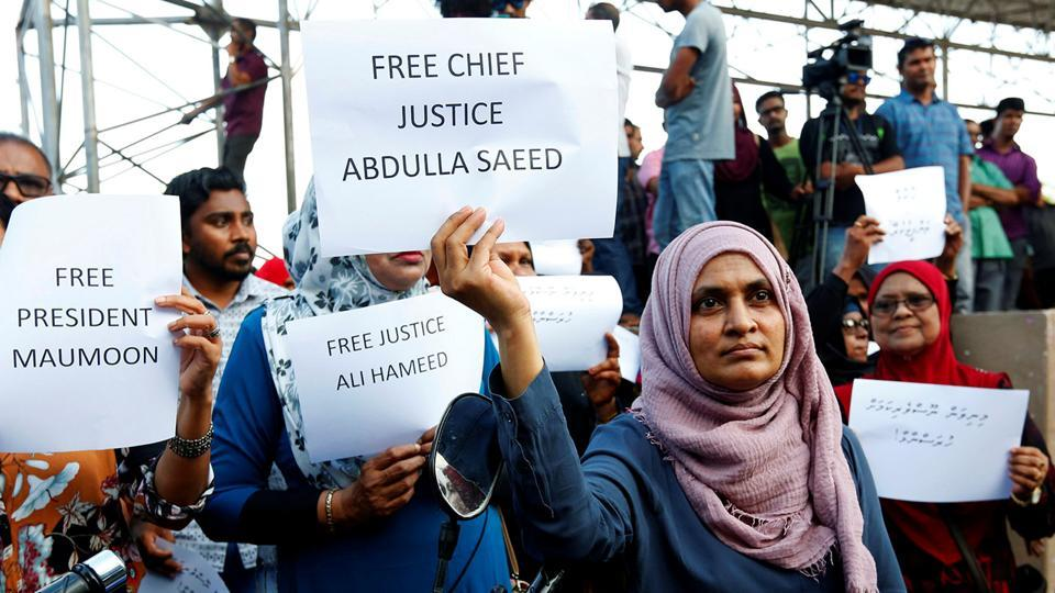 Maldivian opposition supporters holds placards near the main opposition Maldives Democratic Party (MDP) headquarters during a protest against the government on February 9.