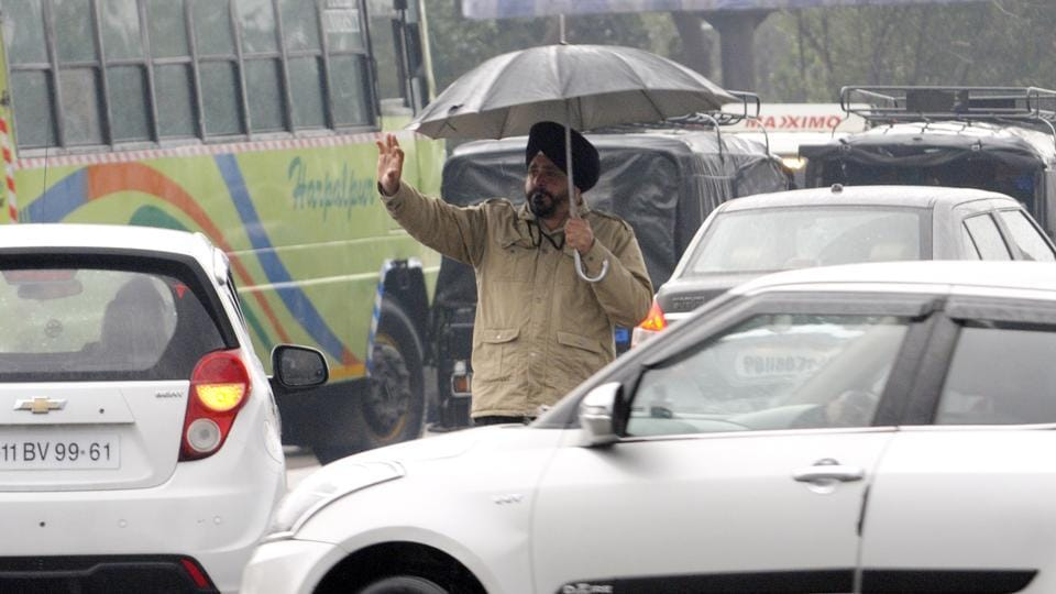 A policeman navigates traffic as it rains at Bus Stand Chowk in Patiala. The northern state of Punjab was also lashed by strong winds and thundershowers on Monday. Jalandhar and adjoining districts including Kapurthala and Nawanshahr recorded rainfall ranging from 8 mm to 10 mm during the early hours on Monday. (Bharat Bhushan / HT Photo)