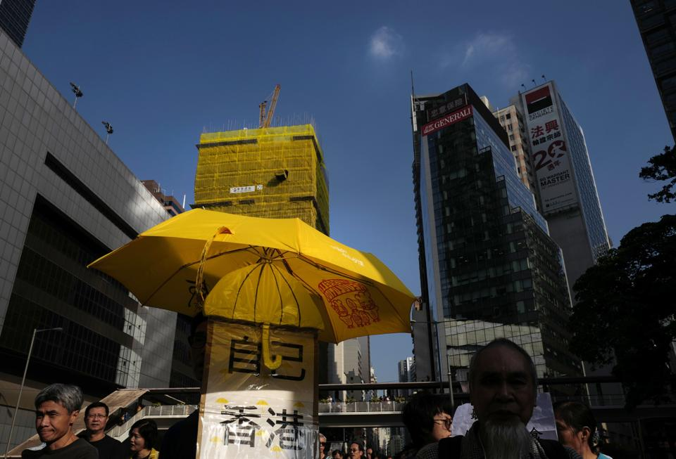 A protester holds a yellow umbrella during a march at a downtown street in Hong Kong on December 3, 2017.