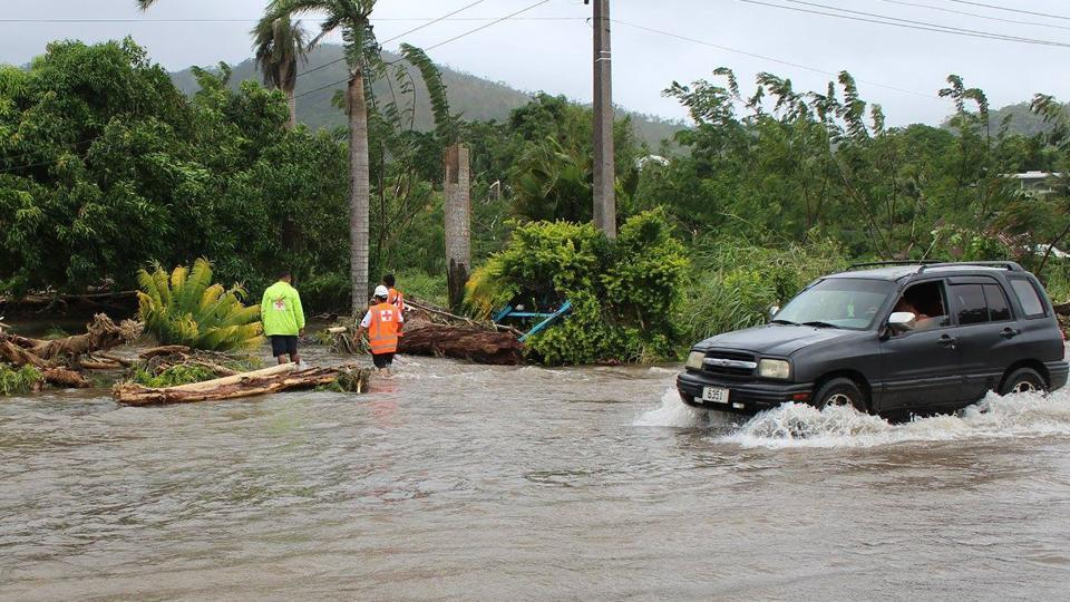 This handout photo shows a car passing through a flooded street as Samoa Red Cross workers check on a house in the Apia area after Cyclone Gita wreaked havoc on the island.
