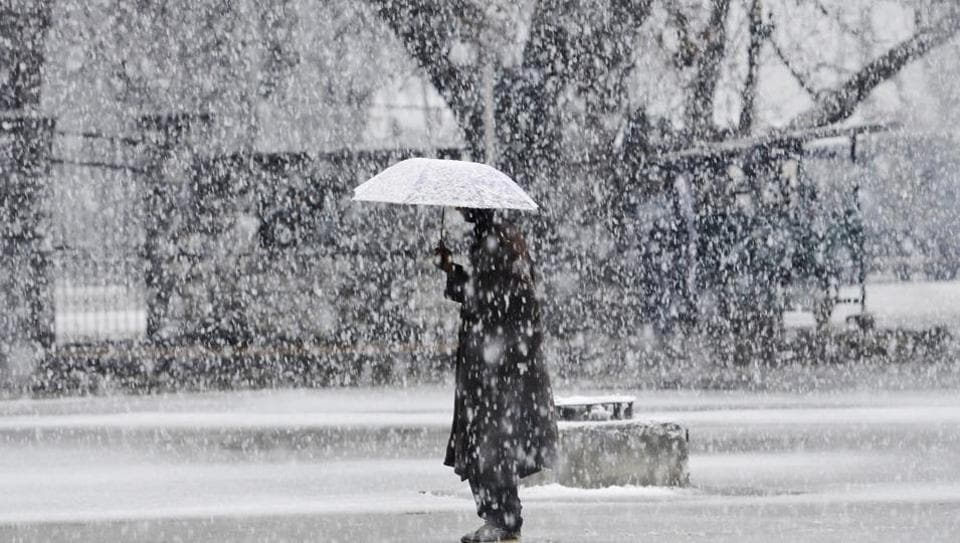 A man stands with an umbrella during snowfall in Srinagar. Kashmir was draped in white on Monday after heavy snowfall through the day punctuated what has been a dry winter so far. This was the year's first major snowfall in Kashmir this winter. (Waseem Andrabi / HT Photo)