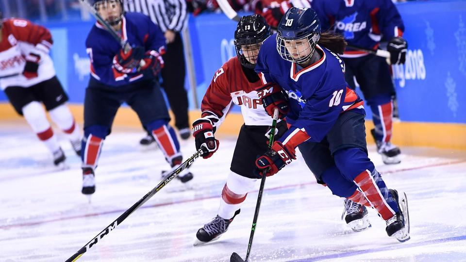 Japan's Moeko Fujimoto (L) and Unified Korea's Choi Jiyeon chase the puck in the women's preliminary round ice hockey match during the Pyeongchang 2018 Winter Olympic Games at the Kwandong Hockey Centre in Gangneung on Wednesday.