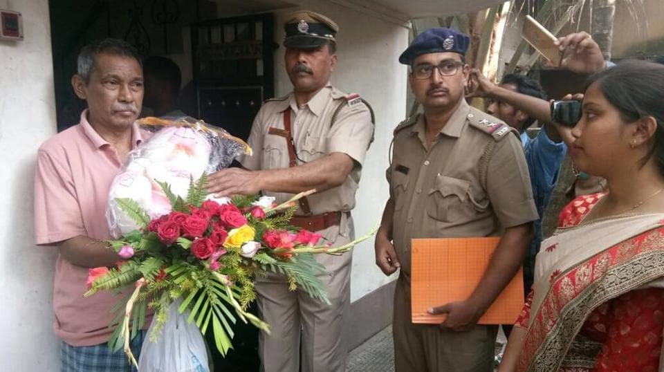 Raghunath Roy, father of Shankar Roy, receiving flowers and gifts from the police officers on Wednesday in Raiganj.