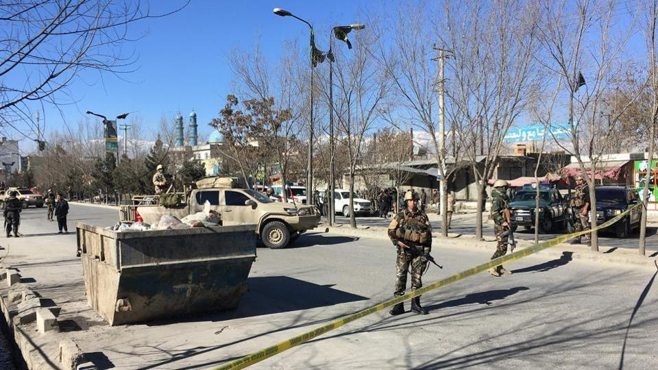 Afghan security forces stand guard near the site of an attack in Kabul.