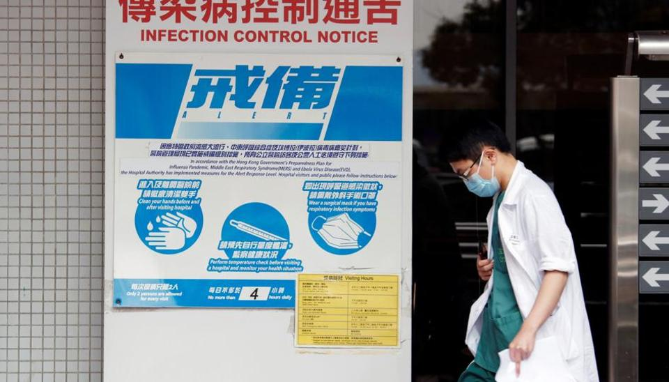A medical personnel walks past a notice on flu alert at a hospital Hong Kong, China.