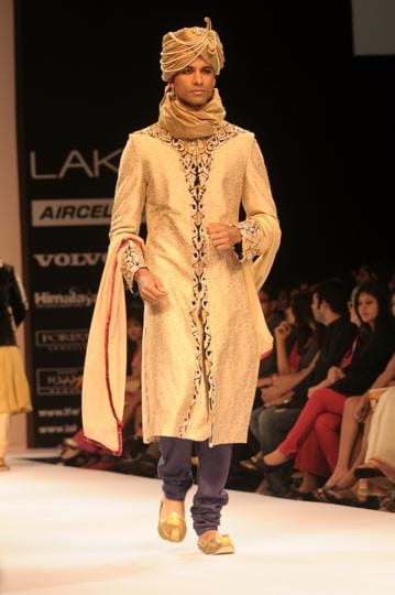 Models walk in traditional attire on the ramp.