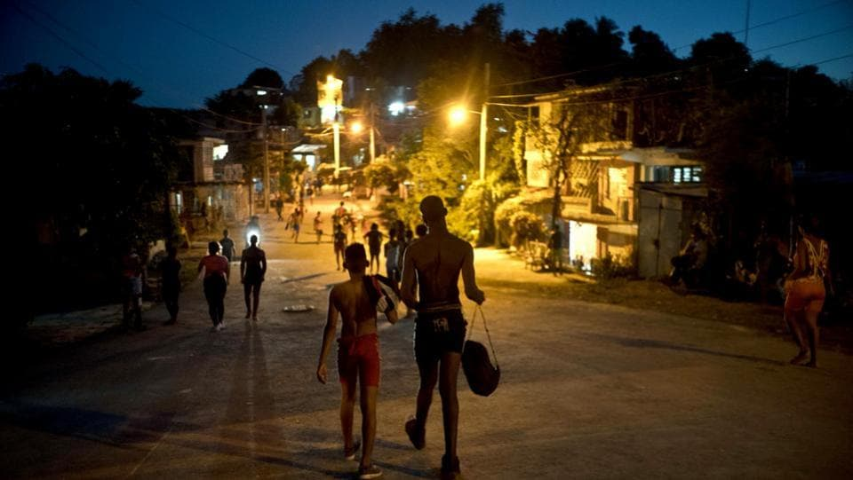 Two visiting wrestlers walk back to the home that's hosting them. Heredia, who has been conducting trains for 38 years, says his dream is to one day create a professional wrestling school that can feed Cuban youths' appetite for the sport. (Ramon Espinosa / AP)