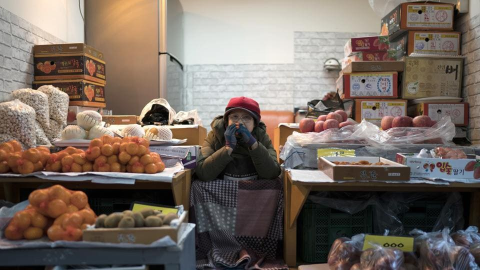 A woman selling fruits waits for customers at the street market in Gangneung, South Korea. While the Winter Olympics unfold in the nearby mountains with hordes of international athletes competing in high-stakes events, closer to the coast, life maintains its laid-back pace evident in this street market.  (AP)