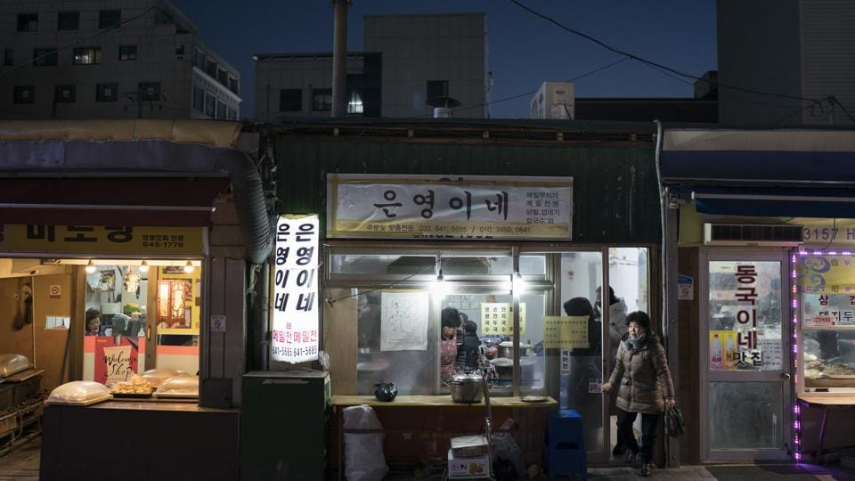 A woman leaves a restaurant in Gangneung, South Korea. Markets in South Korea can range in size from simple gatherings held every five days or so in some rural areas to the massive Namdaemun market area in Seoul, which houses more than 10,000 stores selling anything from fur coats to sneakers to deep-fried shrimp balls. (Felipe Dana / AP)