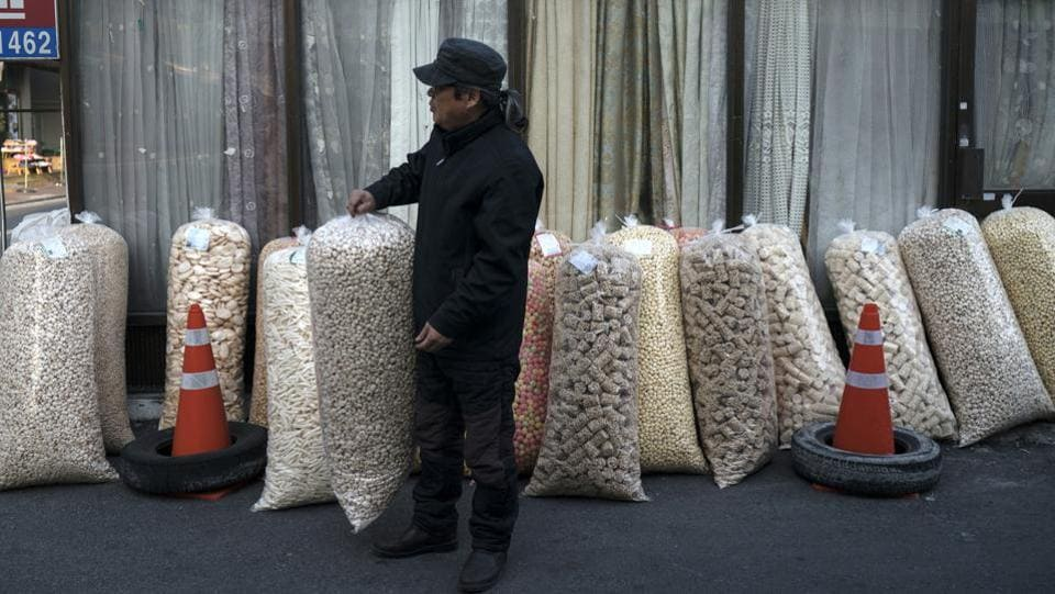 A man lines up large bags of popped grains at his stall in the market. Such markets are a common sight across South Korea and popular among housewives. Local farmers bring fresh vegetables and seasonal fruits here, and stores sell kimchi, special snacks or other knick-knacks at prices much cheaper than stores. (Felipe Dana / AP)