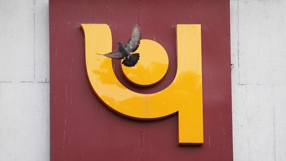 A pigeon flies past the logo of Punjab National Bank outside a branch of the bank in New Delhi on February 15.