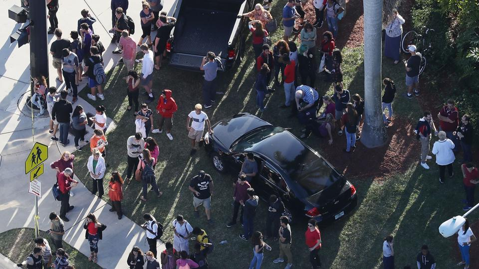 People wait for loved ones as they are brought out of the Marjory Stoneman Douglas High School after a shooting at the school on February 14, 2018 in Parkland, Florida. A 19-year-old former student gunned down at least 17 people, including students and staff, and injured 15 in a Florida high school on Wednesday afternoon. (Joe Readle / Gety Images / AFP)
