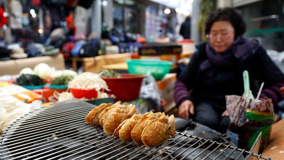 A local seller cooks snacks at the market in Gangneung. Tourists can be sure to never be far from delicious eats with street food being cheap and fast. From favourites like mandu dumplings, to meat skewers and bibimbap cravings  --there's something for all tastes. (Leonhard Foeger / REUTERS)