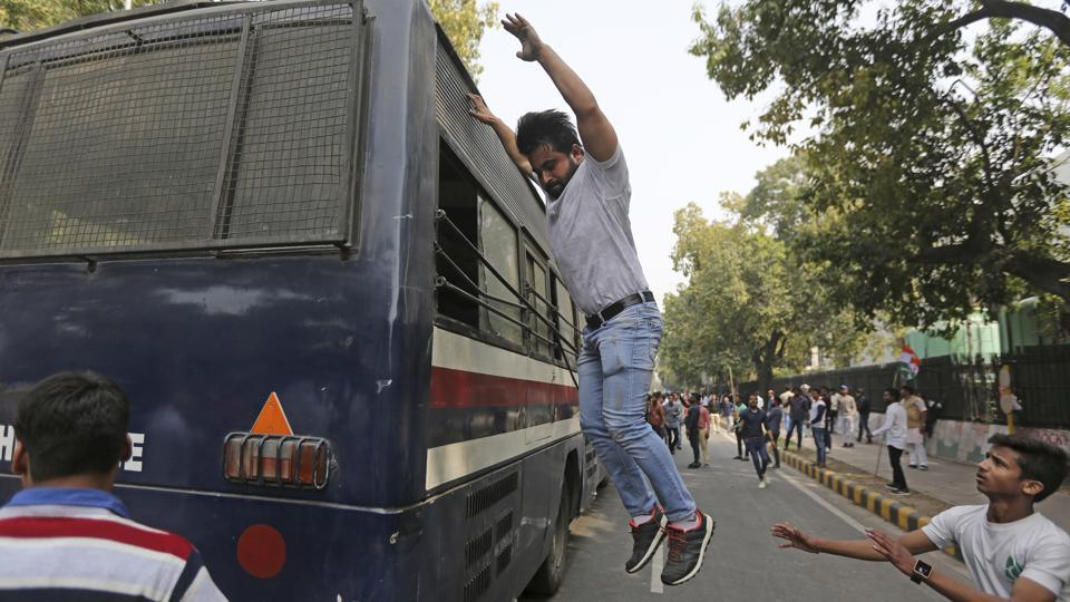 An activist of Congress party's youth wing jumps from the roof of a police bus after being detained during a protest against the Bharatiya Janata Party in New Delhi. The protestors were reacting to reports of an alleged Rs 11,400-crore fraud case by Nirav Modi at a Mumbai branch of the Punjab National Bank. (Altaf Qadri / AP)