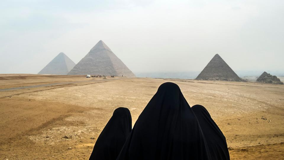Women in veils look at the Great Pyramids of Giza from a vantage point across the Giza plateau, on the south-western outskirts of the Egyptian capital Cairo. (Khaled Desouki / AFP)