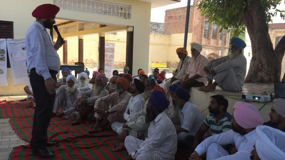Dr Sukhcharan Gosal, former deputy director with the animal husbandry department, and now a master trainer with UDAY social enterprise project, addressing villagers near Sangrur.