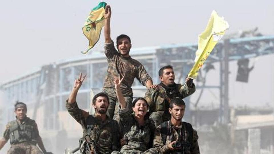 Syrian Democratic Forces (SDF) fighters ride atop military vehicles as they celebrate victory in Raqqa, Syria.
