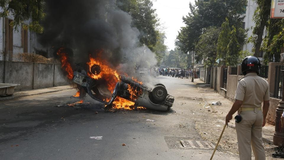 A car is set on fire by a mob during a protest in Ahmadabad on Sunday.
