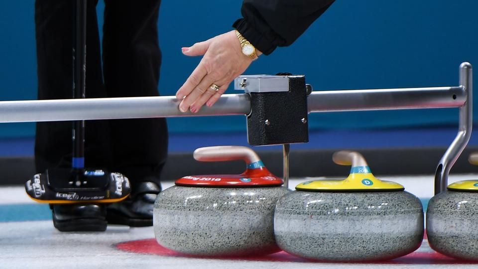 A judge measures during the women's curling round robin session between the Olympic Athletes from Russia and Switzerland during the Pyeongchang 2018 Winter Olympic Games at the Gangneung Curling Centre in Gangneung on February 19, 2018.