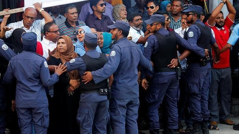 Maldivian Police officers push back the opposition supporters near the main opposition Maldives Democratic Party (MDP) headquarters.