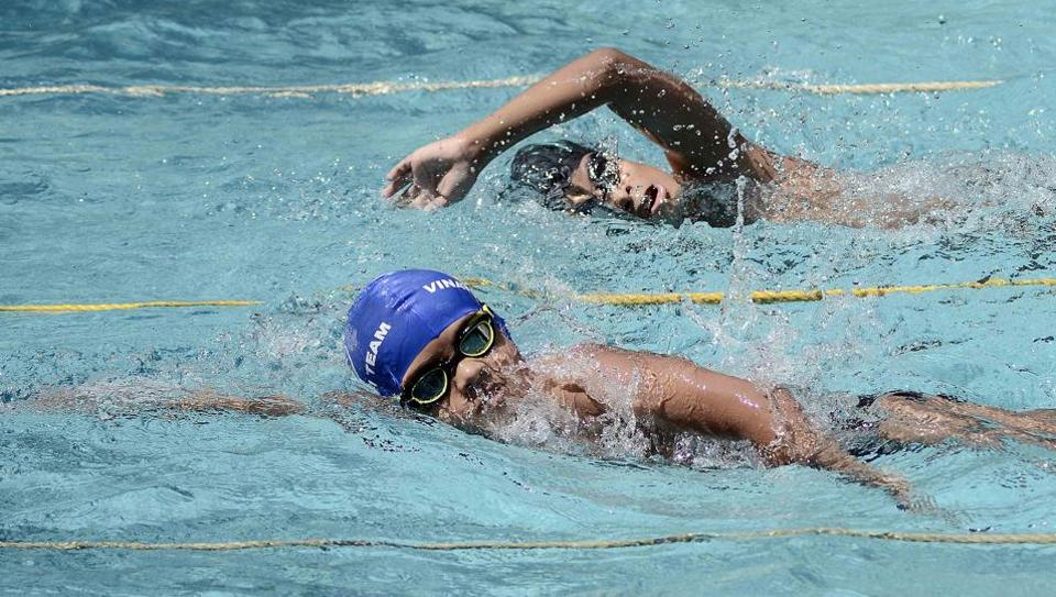 Arnav Bhadekar from Pune (Blue cap) and Rishabh Das from Mumbai (Black cap) swam side by side and both bagged the first place during the 1st All India Invitation Swimathon, organised by Champion Aquatic Club at NG Nande swimming pool, on February 18.  (Ravindra Joshi/HT PHOTO)