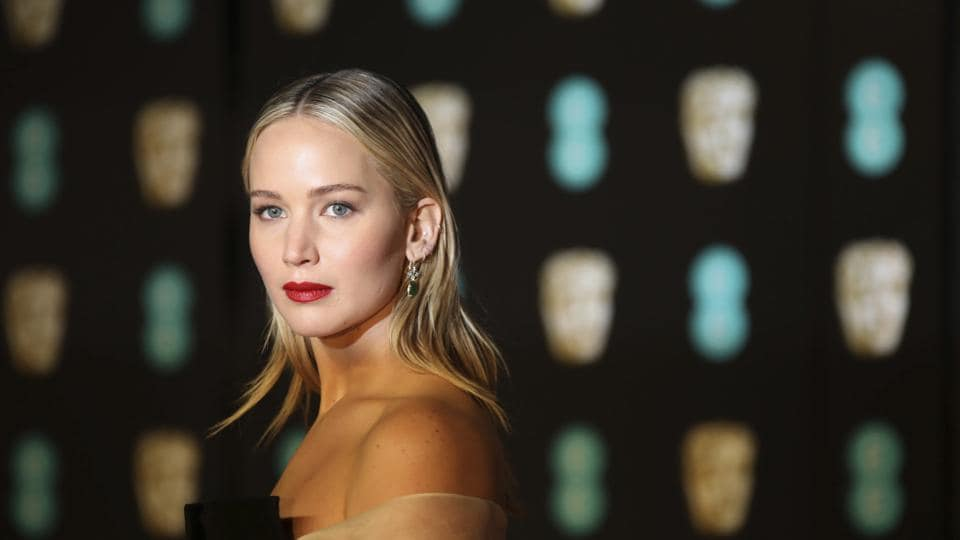 Actress Jennifer Lawrence poses for photographers upon arrival at the BAFTAs.