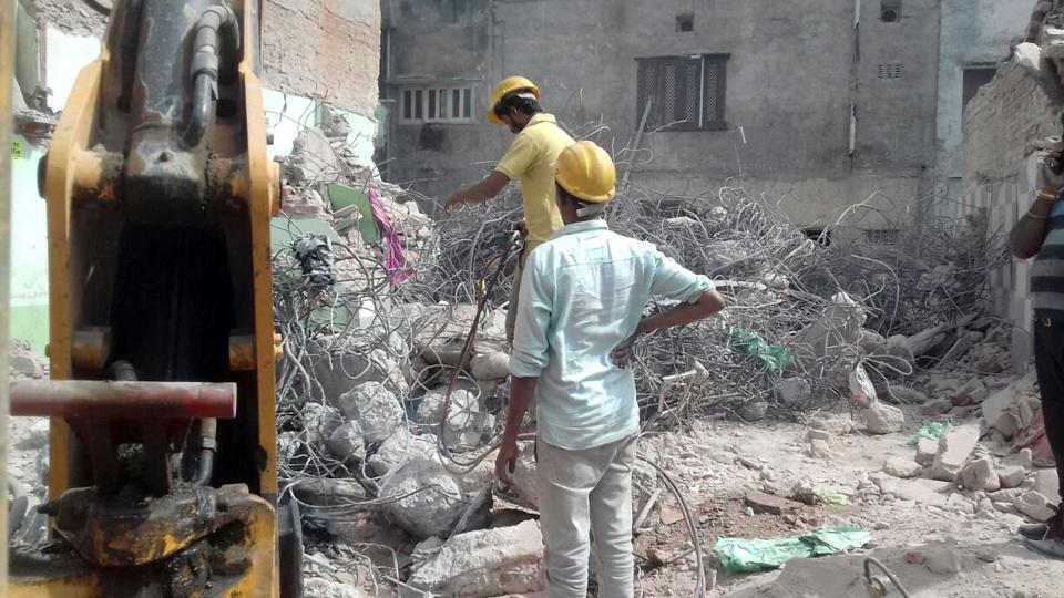 Officials remove debris at the site of cylinder blast  in Beawar.