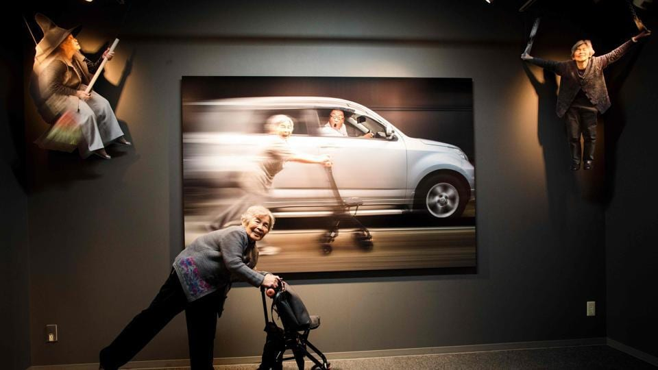 Nishimoto gestures in front of her picture on the opening day of her photo exhibition in Tokyo which took place in December.  This was her first solo exhibition. (Behrouz Mehri / AFP File Photo)