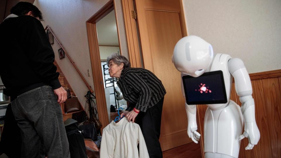 Sassy octogenarian, who has three grandchildren and six great-grandchildren, consults with her son Kazutami (L) to select a costume for a photoshoot. These days Nishimoto lives with a humanoid robot called Pepper, bought for her by her son. (Behrouz Mehri / AFP File Photo)