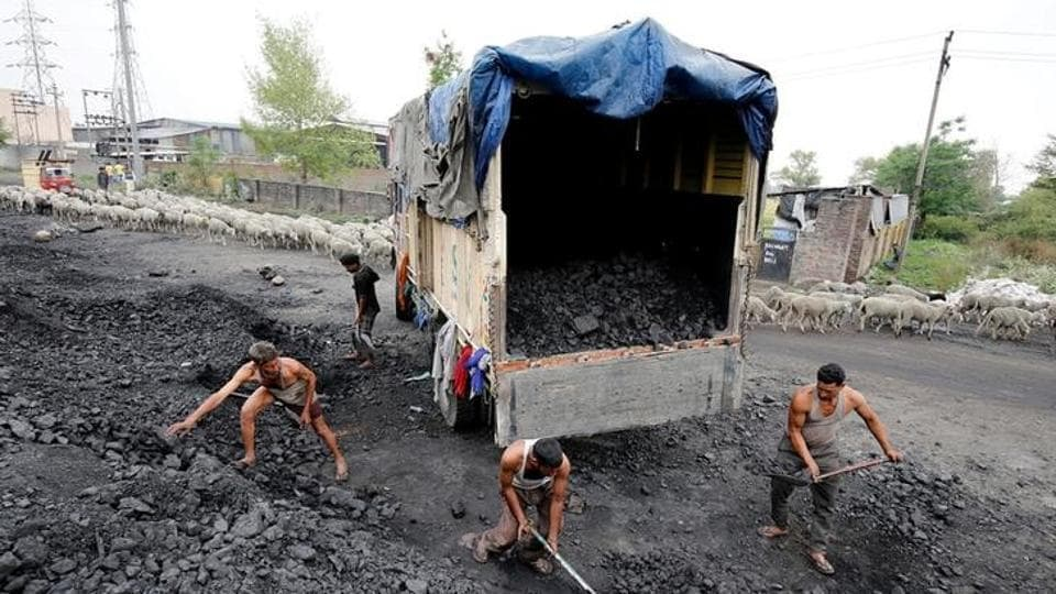 Labourers load coal onto a supply truck on the outskirts of Jammu.