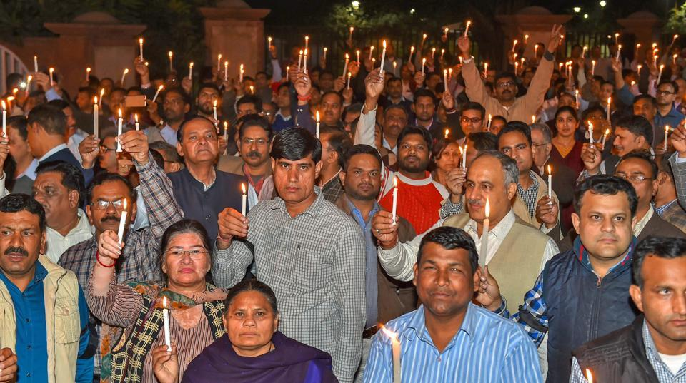 IAS officers and government officials take part in a candle light march protesting the alleged manhandling of Delhi chief secretary Anshu Prakash by AAP MLAs, at Rajghat in New Delhi on Tuesday.