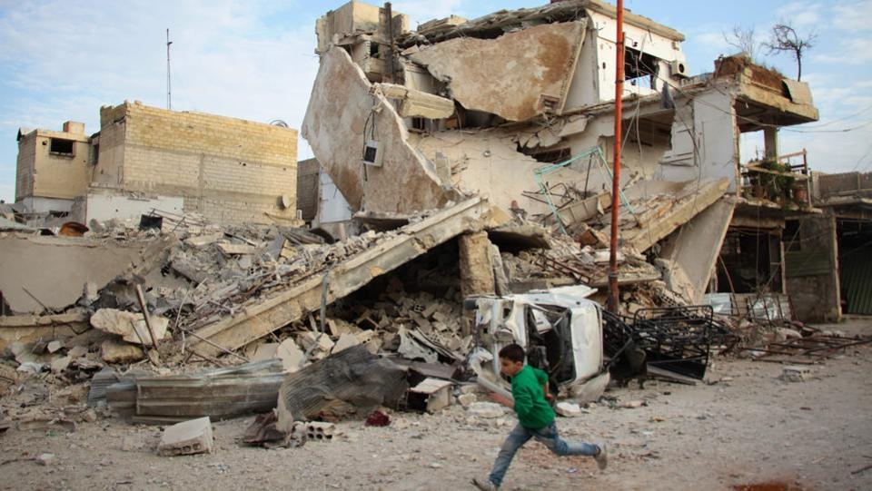 A Syrian boy runs past a destroyed building during air strikes by regime forces. The two main factions in Ghouta, which include Failaq al-Rahman, accuse Moscow and the Syrian army of breaching the de-escalation agreements. (Hamza Al-Ajweh / AFP)