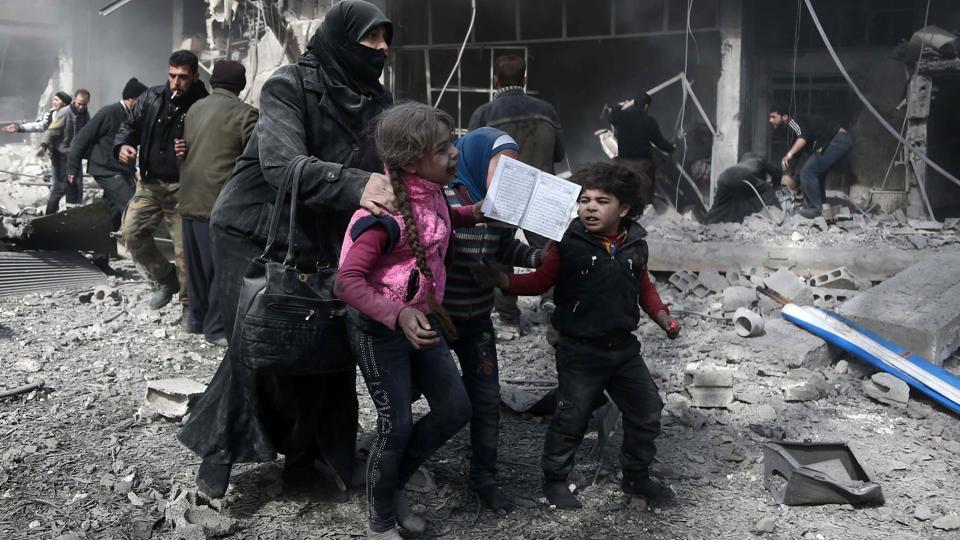 A Syrian woman and children run for cover amid the rubble of buildings following government bombing in Damascus. Eastern Ghouta, which houses around 400,000 residents, has remained under a crippling regime siege for the last five years.  (Abdulmonam Eassa  / AFP)