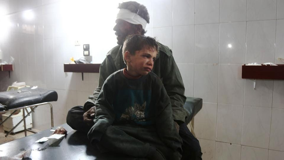 A Syrian child injured in the government bombing cries as he sits with his father at a makeshift hospital in  Hamouria, Damascus. Neither the Syrian military nor Russia commented on the renewed bombardment , but they have often said they do not target civilians.  (Abdulmonam Eassa  / AFP)