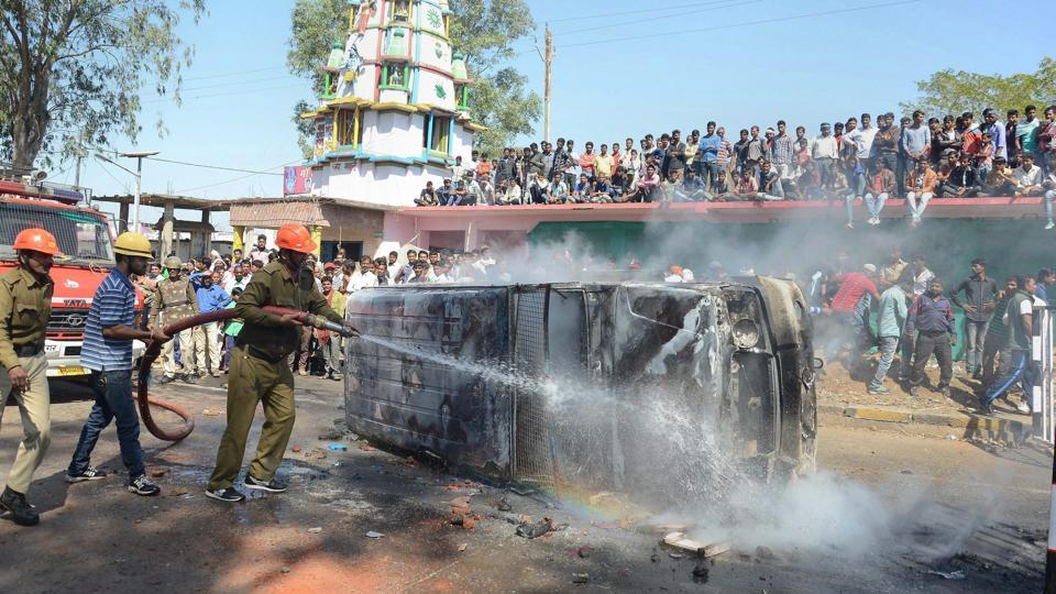 Firemen attempt to douse a fire in a police van, set by an angry mob  following a incident in which a speeding truck rammed into a house and a shop at Barela in Jabalpur. (PTI)