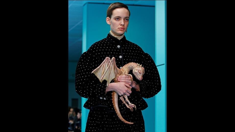 "A man in a long black skirt and jacket covered with crystals, carried a pet dragon made of plastic during the show. A style note said that different designs embodied Gucci's concept of ""pluriverse"" and drew inspiration from Donna Haraway's ""Cyborg Manifesto,""  a 1984 essay rejecting the idea of rigid boundaries, particularly those separating humans from animals and from machines.  (Tony Gentile / REUTERS)"