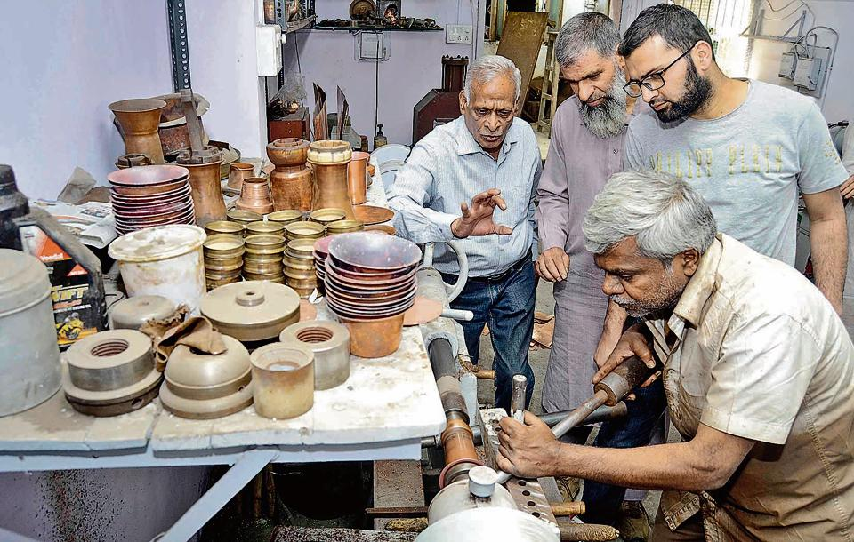 (From left) Bhalchandra Kadu explains the making of a copper glass to Asiam Bhatt and Imtiaz Kak at his workshop in Tambat Aali, Pune