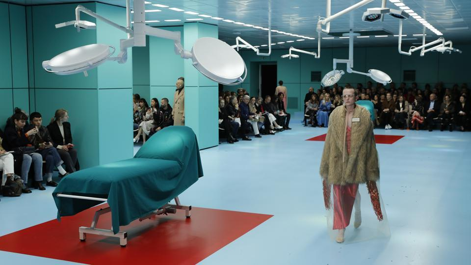 The first shock was when it started on time - almost unprecedented in fashion history. Men and women walked on the runway amid operating tables under bright neon lights in the Gucci Hub, the brand's Milan headquarters, over the steady beeping of a heart monitoring machine.  (Antonio Calanni / AP)