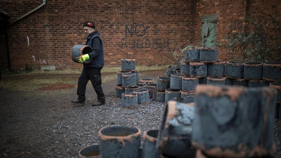 Technician Kevin Titley carries steel drums to the annealing ovens inside the factory. (Christopher Furlong / Getty Images)