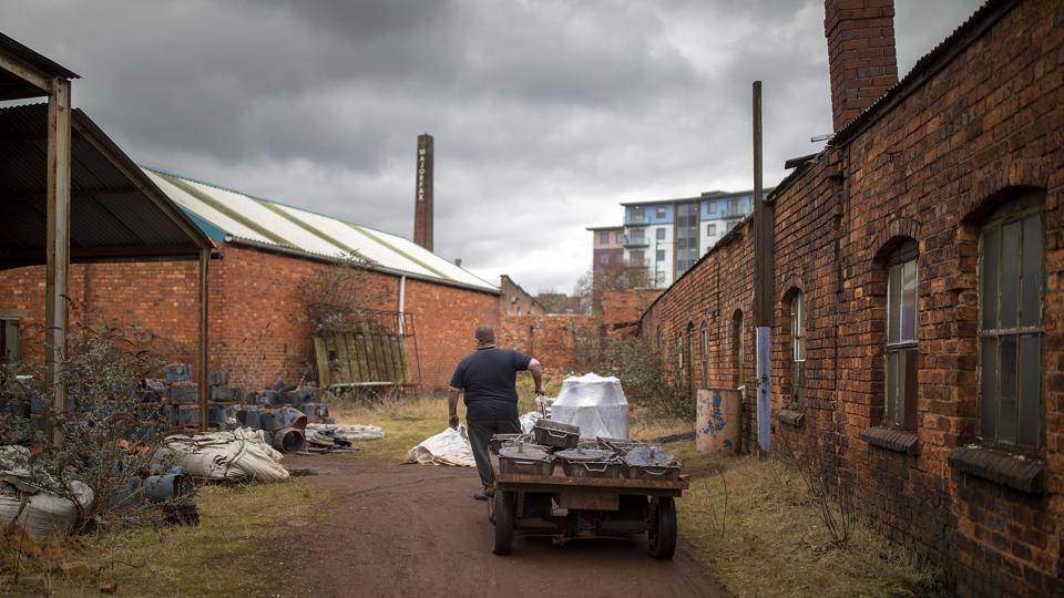 A long shot of the factory as a worker is seen transporting moulded iron work to the ovens inside.  (Christopher Furlong / Getty Images)