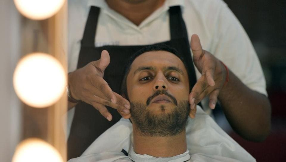 A male hairdresser working with a customer at a men's salon in Islamabad.
