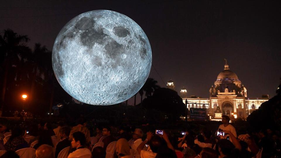 Visitors look at an installation depicting the moon as it is illuminated at the Victoria Memorial in Kolkata on February 17. The 'Museum of the Moon' installation was created by British artist Luke Jerram, with the help of the UK Space Agency. (Dibyangshu Sarkar / Luke Jerram / AFP)
