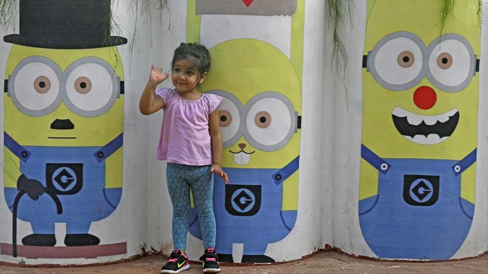 A girl asks her mother to take a photograph of her and her favourite cartoon characters. (Shashi S Kashyap/HT PHOTO)
