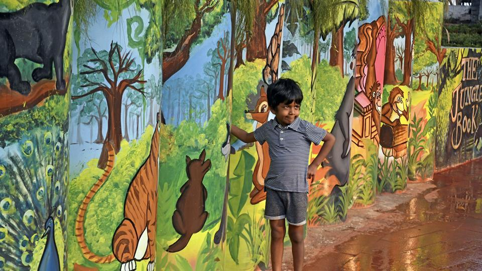 A boy poses against paintings of characters from The Jungle Book. (Shashi S Kashyap/HT)