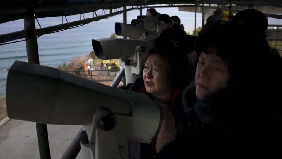 Visitors use binoculars to view North Korea from the Goseong Unification Observatory in South Korea. Parts of the North's Diamond Mountain can be seen from here, where the two Koreas once ran a joint tourism project during a past era of detente. The project stalled after a North Korean soldier fatally shot a South Korean tourist visiting the mountain resort in 2008. (Jae C. Hong / AP)