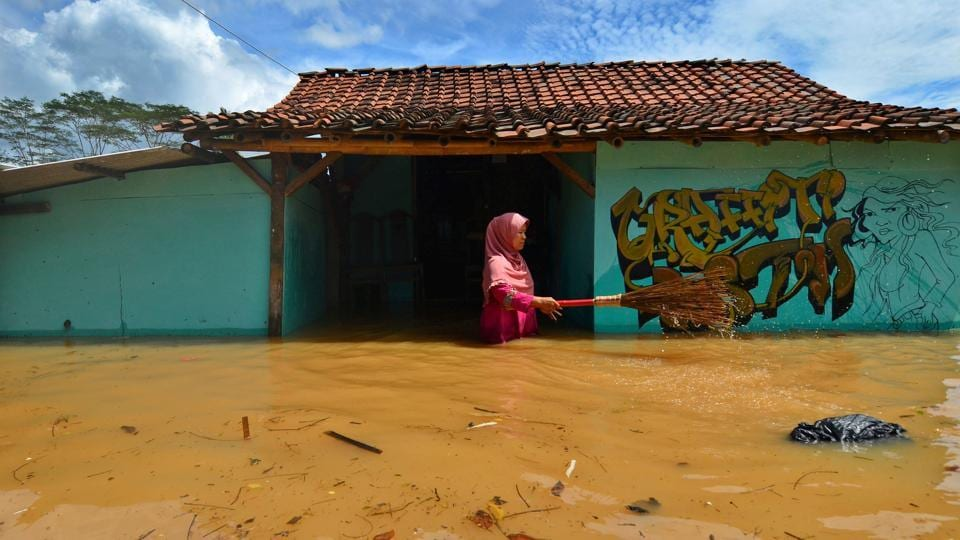 A villager cleans garbage in front of her house as flood hit the Tanjungsari village in Indonesia on February 23. (Adeng Bustomi / Antara Foto / REUTERS)