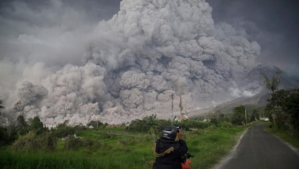 A man photographs Mount Sinabung volcano as it spews thick volcanic ash into the air in Karo, North Sumatra, on February 19. Sinabung roared back to life in 2010 for the first time in 400 years and has remained highly active since. (Endro Rusharya / AFP)